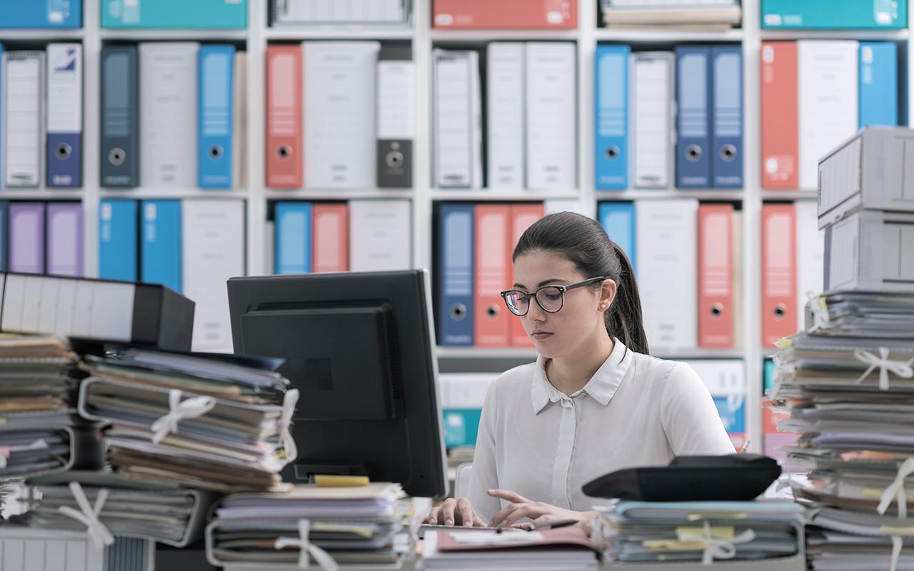 Papierarchiv mit Frau und PC und überfülltem Schreibtisch