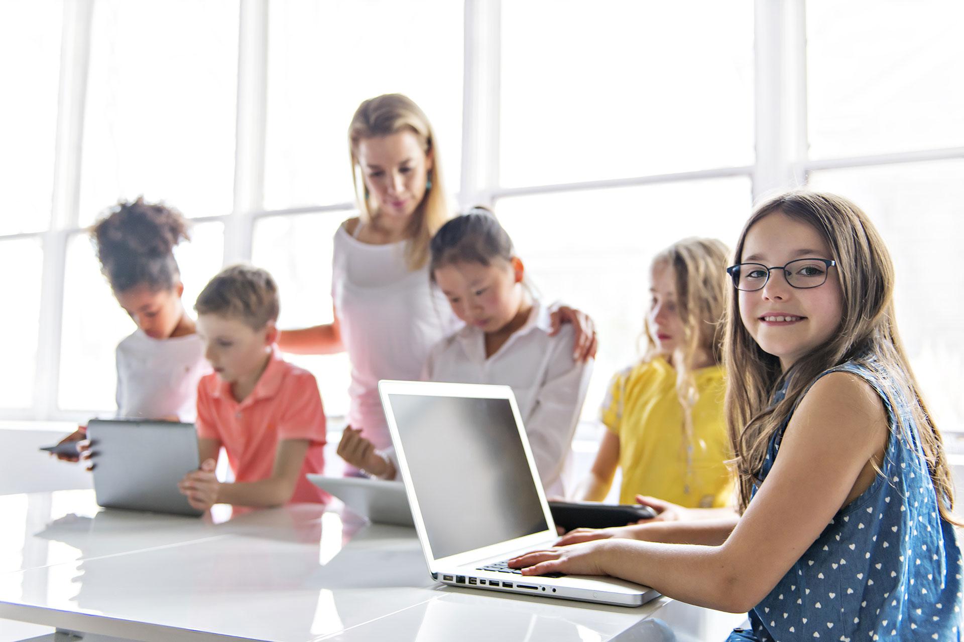 Schüler mit Lehrer im Hintergrund und Laptop